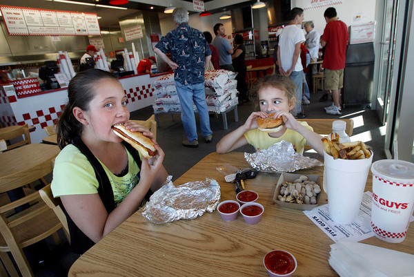 Gloucester: Amanda Kreseskie, 10, of Gloucester and her sister, Kayla, 5, try out a hot dog, hamburger, and fries at Five Guys Burgers and Fries, which opened at Gloucester Crossing yesterday. The two both said the food was good. Photo by Kate Glass/Gloucester Daily Times Monday, September 21, 2009