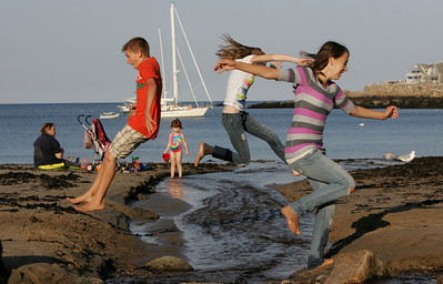 Gloucester: From left, Caden Grooms, 12, Olivia Keating, 12, and Sydney Lovelace, 12, jump over the little creek at Front Beach Thursday afternoon.  Mary Muckenhoupt/Gloucester Daily Times