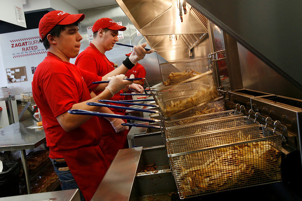 Gloucester: Mark Loiacano of Essex, left, and Tim Labrecque of Gloucester prep fries at Five Guys Burgers and Fries, which opened at Gloucester Crossing yesterday. The business has hired nearly 40 people from around the area. Photo by Kate Glass/Gloucester Daily Times Monday, September 21, 2009