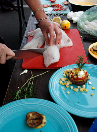 Gloucester: Laurie Lufkin cuts portions of haddock for her panko encrusted haddock during the Seafood Throwdown at the Cape Ann Farmers Market. Photo by Kate Glass/Gloucester Daily Times Thursday, September 17, 2009