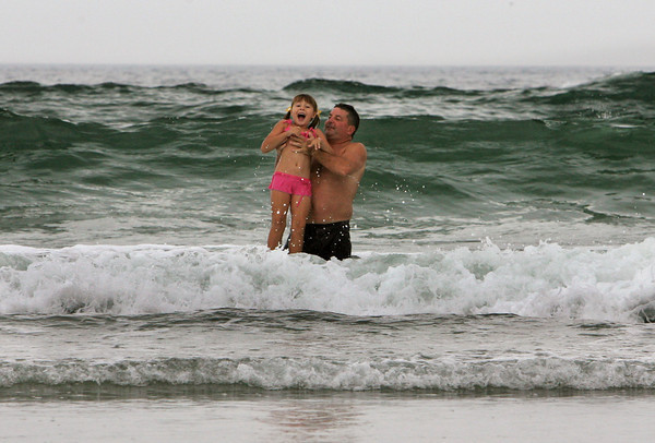 Gloucester: Aran Patrican lifts Sophia Barrett, 7, up over a wave while playing in the heavy surf from hurricane Earl at Good Harbor Beach Friday afternoon.  Mary Muckenhoupt/Gloucester Daily Times