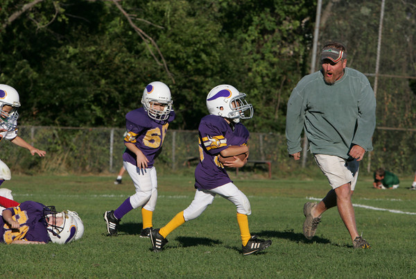 Gloucester: Ryan Bergin, 7, runs the ball past his coach Sam Parker and ahead of teammate Luke Walkama while running drills before the East Gloucester Vikings pee-wee football D team scrimmage Manchester Essex on a field on Dr. Osman Babson Road Wednesday afternoon.  Mary Muckenhoupt/Gloucester Daily Times
