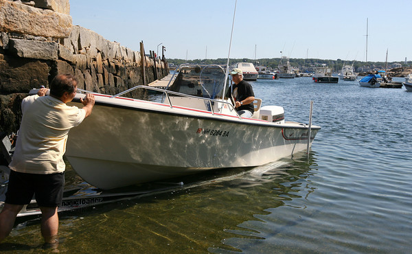 Rockport: Andre Hassan, left, gives his friend, Rai Vianchi, a push as they put their boat in the water at the Old Granite Pier on Tuesday. The two said they were fishing until November last year and are hoping this fall will allow them to do the same. Photo by Kate Glass/Gloucester Daily Times
