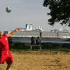 Gloucester: Wilson Deleon serves the ball at Stage Fort Park as the 936-foot Holland America ship sits just inside Gloucester Harbor Wednesday afternoon.  The ship arrived Wednesday morning and amidst heavy rain, but that didn't stop tourists from coming ashore to walk around Cape Ann for the day. Mary Muckenhoupt/Gloucester Daily Times