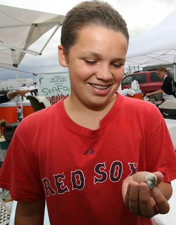 Gloucester: Andrew Widtfeldt, 13, takes a good look at a bluefish eye before eating it during the Seafood Throwdown at the Cape Ann Farmers Market yesterday afternoon. Widtfeldt said it was the first fish eye he had ever eaten and it tasted fishy. Photo by Kate Glass/Gloucester Daily Times