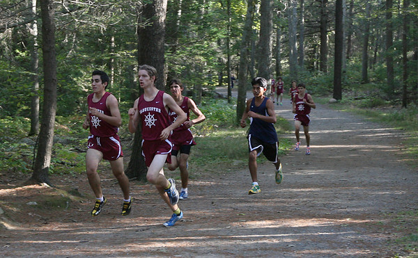Gloucester: From left: Gloucester's Caulin Rogers, Wes Dunn, Noah Mondello, and Winthrop's Alejandro Miranda break away from the pack at the start of their cross country meet at Ravenswood Park yesterday. Dunn won the race with a time of 15:55. Photo by Kate Glass/Gloucester Daily Times