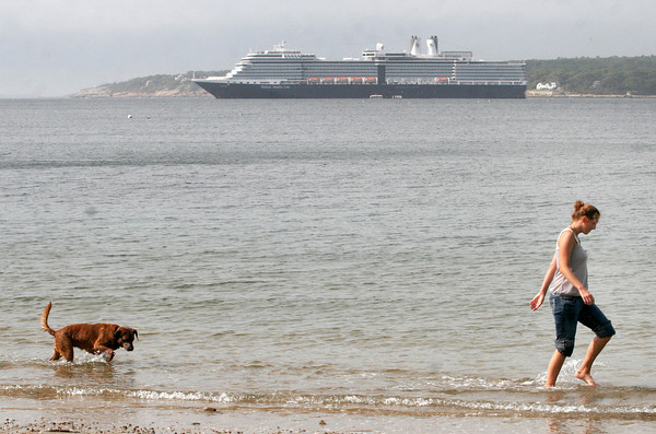 Gloucester: Tammi Wilke walks with her roomate's dog, Memphis, along Niles Beach yesterday morning as the cruise ship Eurodam anchors in Gloucester Harbor. The ship, which has over 2,000 passengers, will be back to Cape Ann on October 13th. Photo by Kate Glass/Gloucester Daily Times