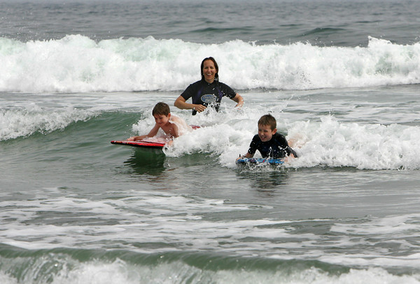 Gloucester: Holly Markham watches as her sons, Jimmy, 8, left, and Owen, 10, ride a wave while playing in the high surf from hurricane Earl at Good Harbor Beach Friday afternoon.  Holly said she wasn't too worried about the storm and was having fun in the waves. Mary Muckenhoupt/Gloucester Daily Times