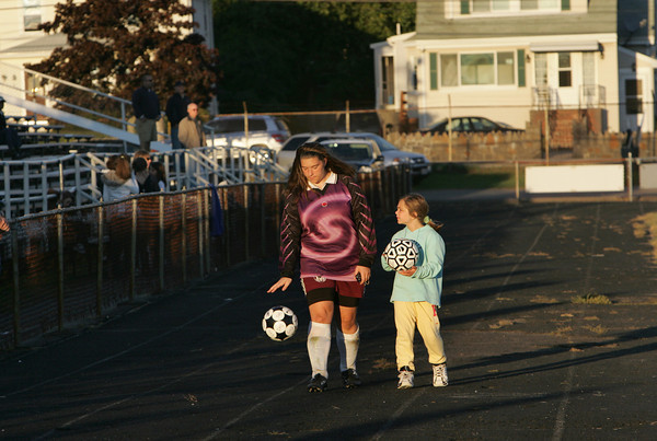 Gloucester: Elizabeth McCormick, 15, and Maeve Pleuler, 8, walk the sidelines of the girls soccer game waiting to hand over a soccer ball when needed at Newell Stadium Wednesday afternoon. Mary Muckenhoupt/Gloucester Daily Times