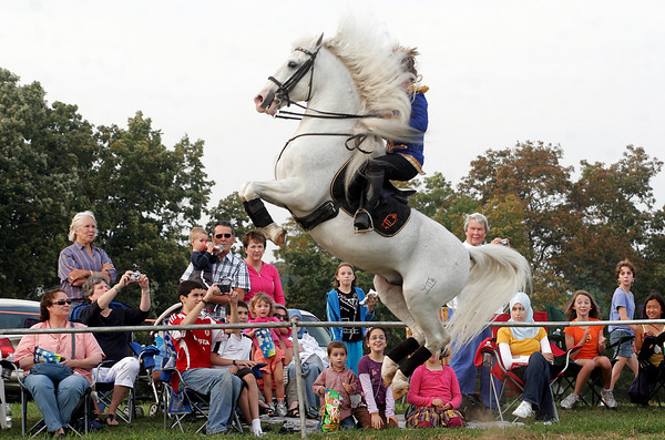Essex: The crowd stares in amazement as Gabriella Herrmann gets her stallion to leap off the ground while performing a courbette at Cogswell's Grant in Essex. Herrmann's Royal Lipizzan Stallions of Austria did three performances at the site over the weekend. Photo by Kate Glass/Gloucester Daily Times