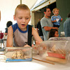 Gloucester: James Payne raises the sails of a miniature ship inside a bottle at one of the activity tables at Maritiem Heritage Days at the Maritime Heritage Center Saturday afternoon.  Walter McGrath of Lanesville taught kids and adults how to make a ship in a bottle as well as tie a bowline, a basic martime knot that is quick to tie and won't slip. Mary Muckenhoupt/Gloucester Daily Times