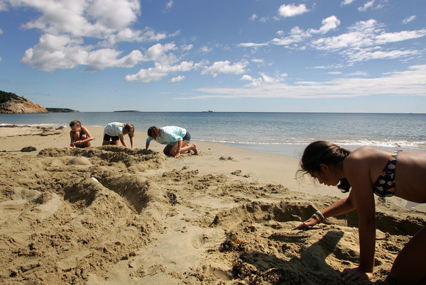 Manchester: Sophia Kressy, right, works on making a starfish in the sand as her friends, from left, Jilly Veidonheimer, Summer Sims and Olivia Frazer work on making a sand igloo while enjoying a warm day at Singing Beach Thursday afternoon. The one concern the girls had was keeping the tide from destroying their sand art. Mary Muckenhoupt/Gloucester Daily Times
