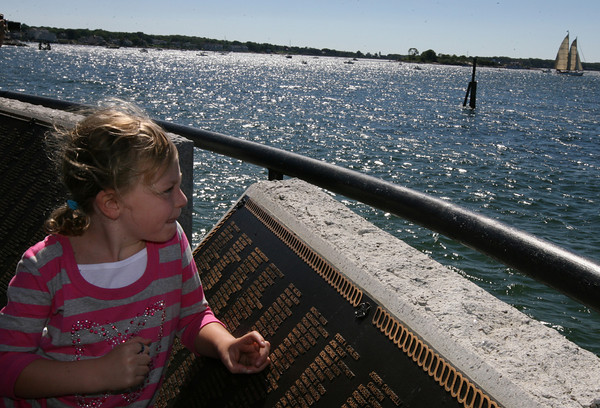 Gloucester: Nora Rockwell watches from the Fishermen's Memorial as the Summerwind passes by during the Parade of Sail yesterday morning. Hundreds of people gathered along Stacy Boulevard for the event. Photo by Kate Glass/Gloucester Daily Times