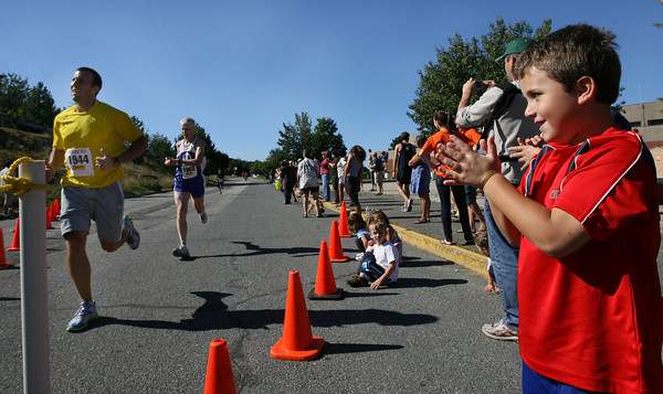 Gloucester: Zachary Oliver, 6, cheers for his father, Michael Oliver, as he finishes the Run the Goose 7K Road Race in Gloucester yesterday morning. Photo by Kate Glass/Gloucester Daily Times