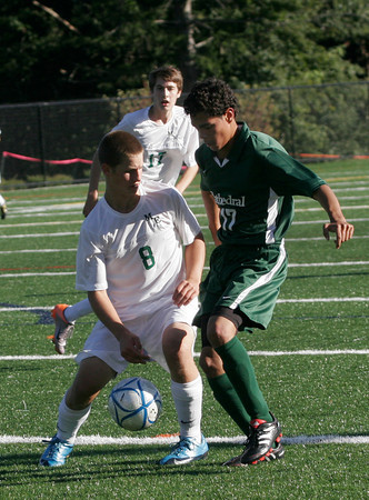 Manchester: Manchester Essex's Alex Walder keeps the ball away from Cathedral's Carlos Pereira during their game at Hyland Field yesterday afternoon. Photo by Kate Glass/Gloucester Daily Times