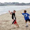 Rockport: Joe Gilligan, 7, runs past his friend Dylan Fahey, 7, as the two play football on Long Beach Saturday morning while enjoying what may be the beach day of year.  Mary Muckenhoupt/Gloucester Daily Times
