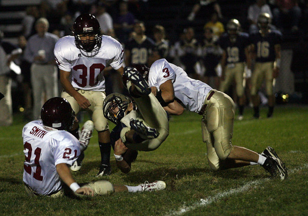 Winthrop: Gloucester's Marc Giacalone tackles Winthrop's Nick McCarthy as Zachary Smith and Matthew Catarino look on during their game in Winthrop last night. Photo by Kate Glass/Gloucester Daily Times