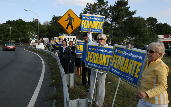 Gloucester: Pat Francis, right, and Linda Devoe hold signs supporting State Representative Ann-Margaret Ferrante at Grant Circle yesterday evening as supporters of Janet Holmes, who is running a write-in campaign for the republican spot on the ballot opposite Ferrante, stand further down. Polls are open today for the primary election. Photo by Kate Glass/Gloucester Daily Times