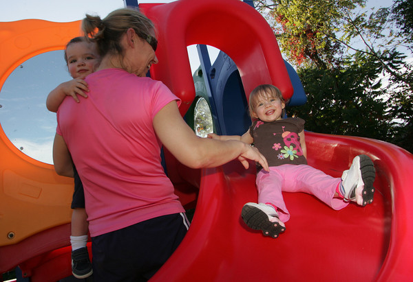 Rockport: Heather Dewan helps her daughter Caitlin, 18 months, down the slide while holding Caitlin's twin brother Liam as they play at the toddler playground next to Rockport Elementary School Wednesday afternoon.  Dewan says she likes taking her kids to this playground, which is open after school and on weekends, because the structures are very managable for younger kids. Mary Muckenhoupt/Gloucester Daily Times
