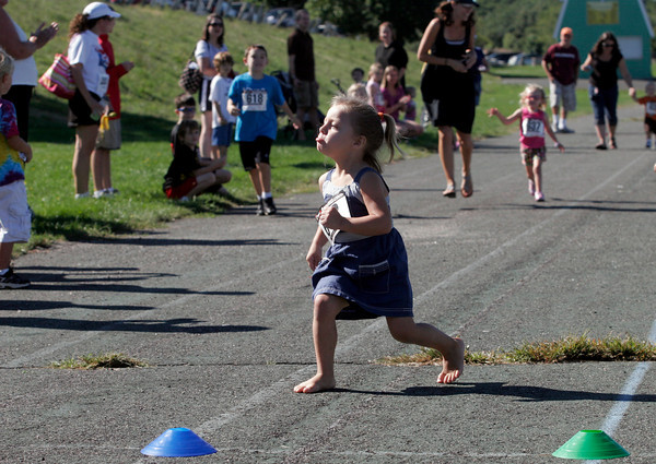 Gloucester: Olivia Savino, 3, makes a face at her parents just before crossing the finish line to win the 2-3 year-old kids race at O'Maley Middle School on Monday. Savino ran the whole race barefoot. Photo by Kate Glass/Gloucester Daily Times
