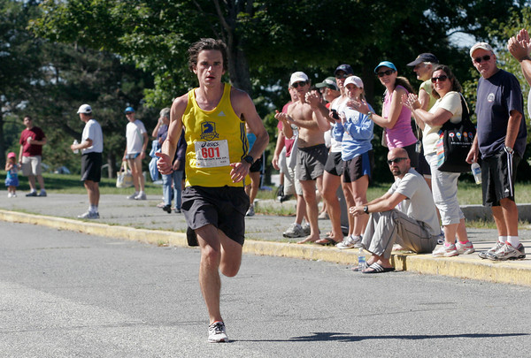 Gloucester: Spectators applaud as Patrick Moulton approaches the finish line to win the 77th Around Cape Ann 25K Road Race yesterday morning. Photo by Kate Glass/Gloucester Daily Times