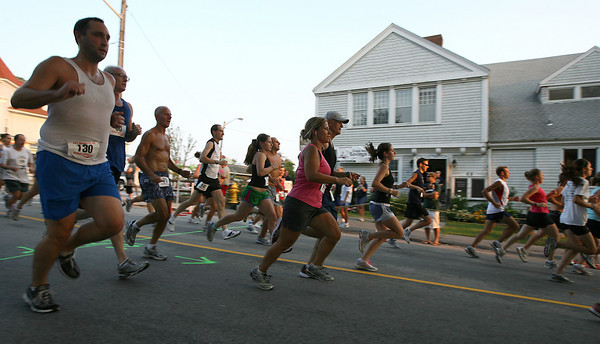 Gloucester: Runners pass the Magnolia Library Center at the start of the 34th Annual Magnolia 5K Road Race yesterday evening. Proceeds from the race go toward the Magnolia Library Center. Photo by Kate Glass/Gloucester Daily Times
