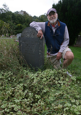 Gloucester: Peter Anastas, President of the Charles Olson Society, kneels at the site of the poet's grave at Beechbrook Cemetery in Gloucester. An effort is underway to repair the stone, which is cracked. Photo by Kate Glass/Gloucester Daily Times