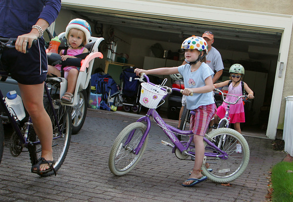 Manchester: Madeline Lai, 7, heads out of the driveway after her mother Stacey and sister Addison, 2, with her sister Calista, 5, and father Steve, behind as they all head out for a family bike ride from their Manchester home Saturday morning. Mary Muckenhoupt/Gloucester Daily Times