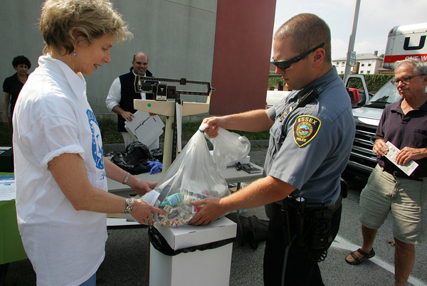 Gloucester: Essex police officer Greg Brown puts the bag of prescription drugs collected from the town of Essex on top of a box of prescription drugs from Gloucester on a scale behind the Rose Baker Senior Center Saturday afternoon.  Saturday was National Drug Drop-Off Day and members of the Healthy Gloucester Collaborative, including Joan Whitney, left,director of substance abuse prevention, helped collect drugs from Gloucester residents, with drop off spots in Essex and Rockport as well.  About 70 lbs. of drugs were collected Saturday before the National Guard came to collect them. Mary Muckenhoupt/Gloucester Daily Times
