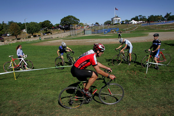 Gloucester: A competitor in the Master Men's race rides by as cyclysts wait to cross the race course durng the 12th annual Gran Prix of Gloucester cyclocross race held at Stage Fort Park Saturday morning.  Hundreds of cyclists came to Gloucester to compete in the two day event which turns the park into a zig-zag race course.  Mary Muckenhoupt/Gloucester Daily Times