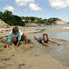 Manchester: Jilly Veidonheimer acts as a human barrier between the tide and the creations she made in the sand with her friends Olivia Frazer and Summer Sims, left, while enjoying a warm day at Singing Beach Thursday afternoon. Mary Muckenhoupt/Gloucester Daily Times