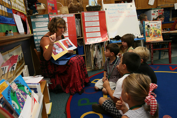 Manchester: Wendy Manninen, a kindergarten teacher at Manchester Memorial Elementary School, teaches sign language to five of her students during the first day of school yesterday. Kindergarteners came to the school in groups of five so they could get used to the classroom and their parents could fill out paperwork. Photo by Kate Glass/Gloucester Daily Times