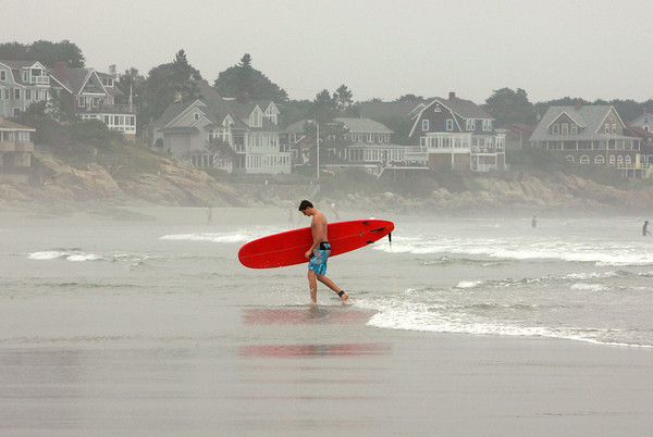 Gloucester: Ian Knechtle walks out of the water at Good Harbor Beach after taking advantage of the waves from hurricane Earl Friday afternoon. Mary Muckenhoupt/Gloucester Daily Times