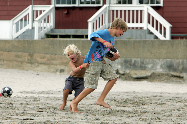 Gloucesteer: Ben Merdock, 6, of Gloucester tries to take down his big brother Quinn, 10, while playing football at Good Harbor Beach Friday afternoon.  Mary Muckenhoupt/Gloucester Daily Times
