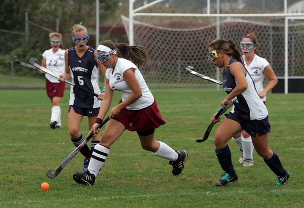 Gloucester: Gloucester's Hilary Rose Ellis keeps the ball ahead of Swampscott defenders during the field hockey game at Newell Stadium Thursday afternoon. Mary Muckenhoupt/Gloucester Daily Times