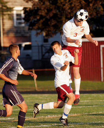 Gloucester: Gloucester's Connor Olson leaps above his teammate, William Dixon, for the ball during their game against Swampscott at Newell Stadium last night. Photo by Kate Glass/Gloucester Daily Times