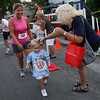 Gloucester: Sereda Blum pats Ava Herrera, 3, on the head after finishing the Magnolia Fun Run with her mom, Michele Herrera, on Thursday evening. Ava was motivated to run with the promise of a popsicle at the end of the race. Photo by Kate Glass/Gloucester Daily Times
