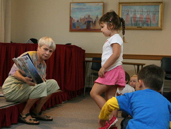 Rockport: Charlotte Mento tries to get a closer look at the pictures as Sarah Clark reads Pout Pout Fish in the Big Big Dark during story hour at the Rockport Public Library on Tuesday morning. Photo by Kate Glass/Gloucester Daily Times
