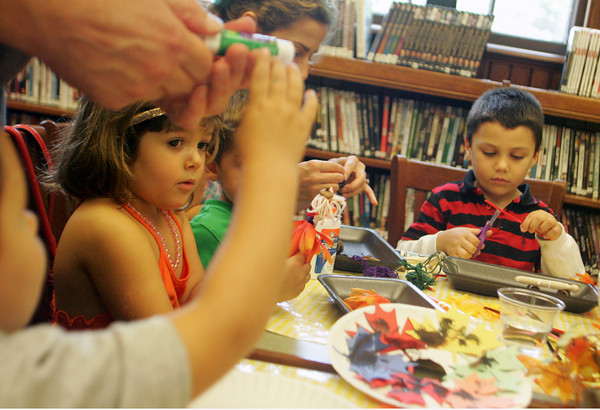 Manchester: Children at the Manchester Public Library including Lily Stefanovich, 4, and Marco Bussone, 5, right, work on arts and crafts during fall stories and crafts hour Saturday monring. Mary Muckenhoupt/Gloucester Daily Times