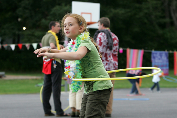 Essex: Eden Mayer, 8, stays focused while hula hooping at a hula themed back to school party held behind the Essex Elementary School Friday evening. The night included hula hooping and hula dancing and other fun activities for students and their families. Mary Muckenhoupt/Gloucester Daily Times