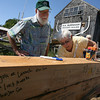 Essex: Joe Boyd and Judy James sign the keel of the Pinky Schooner Ardelle during Frame Up! In the Basin at the Essex Shipbuilding Museum and H.A. Burnham Boat Building yesterday. The schooner build will be ongoing throughout the year. Photo by Kate Glass/Gloucester Daily Times