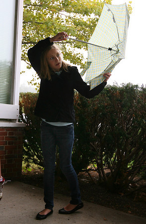 Manchester: Marlena Fulmer twirls her umbrella while waiting for a ride at Manchester Memorial School yesterday afternoon. Rain is forecast again for today. Photo by Kate Glass/Gloucester Daily Times