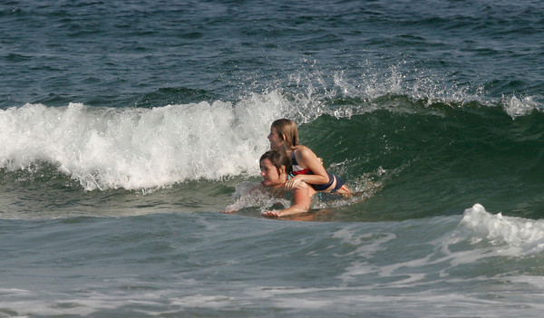 Gloucester: Callie McCauley rides on the shoulders of Robin Sorensen as they play in the waves at Good Harbor Beach on Friday. The weather is supposed to be very warm this weekend despite that fall just began. Photo by Kate Glass/Gloucester Daily Times