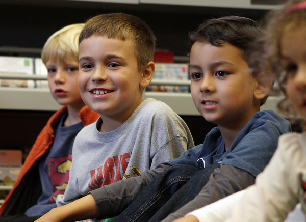 Leo von Herrmann, 8, and Guiseppe Tra, 6, both of Manchester, smile as they watch a pirate puppet show at Manchester Public Library. David Le/Gloucester Daily Times