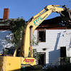 An excavator tears apart the roof of the Washington St. building that was destroyed by Thursday night's fire. The building was deemed unsafe and a collapse hazard so crews from Action Emergency Services worked throughout Friday afternoon to take down the building. David Le/Gloucester Daily Times