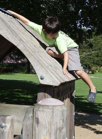 David Le/Gloucester Daily Times. Campbell Pang, 7, of Duxbury, hangs onto the side of a playground roof and prepares to jump to the ground on Friday afternoon at Masconomo Park.