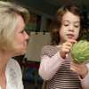 Tami Cronin, a Pre-K and Kindergarten teacher at the Eastern Point Day School, watches as Halia Taylor, 4, points out different parts of an artichoke as part of their science class. David Le/Gloucester Daily Times