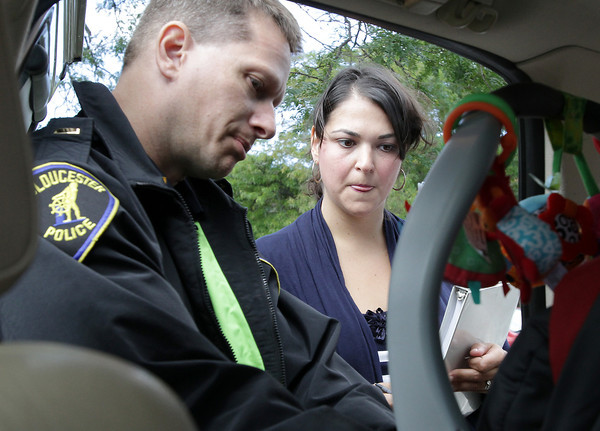 Deborah Taormina, of Gloucester, looks on as Lieutenant Joseph Fitzgerald of the Gloucester Police Department demonstrates how to properly buckle and tighten the seatbelts in her son, Lorenzo's car seat. Lieutenant Fitzgerald ran a Child Passenger Safety Program which offered free child-safety checks and tips on Friday across from the police station. <br /> David Le/Gloucester Daily Times