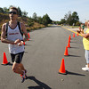 Annette Billings, a YMCA employee cheers on Ben Strain, of Beverly, as he crosses the finish line to win the Run the Goose 7K road race, on Monday morning. David Le/Gloucester Daily Times.