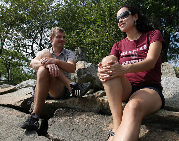 Radek Lyskawka, left, chats with Ingrid Brieto, as they sit on the rocks overlooking Manchester Harbor on Tuesday afternoon. David Le/Gloucester Daily Times.